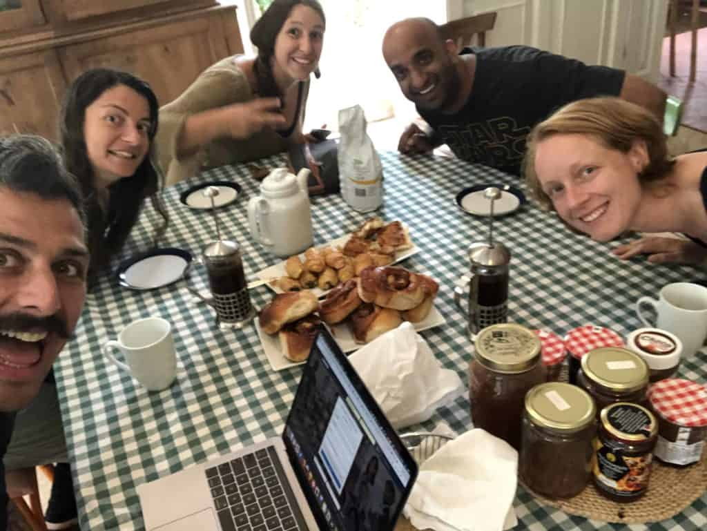 Selfie of the five members of our core research team, sitting around the dining table with a brunch spread of delicious Greek pastries